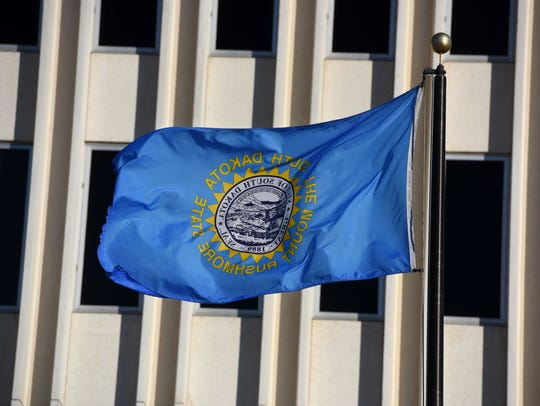 South Dakota's state flag waves in the air outside
