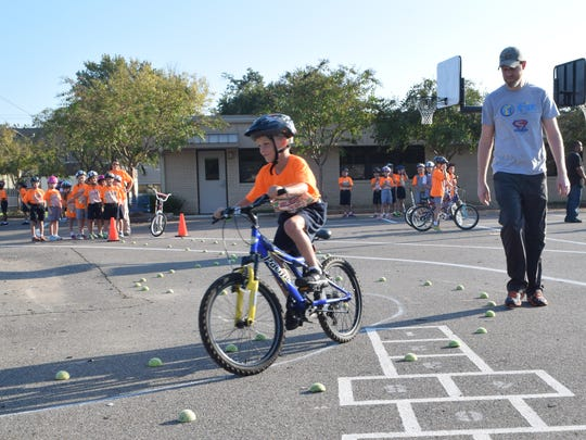 Carson Callahan (left), a third-grader at Our Lady of Prompt Succor, rides through a safety obstacle course Wednesday as Matt Taylor of Fit Families for Cenla looks on. Fit Families for Cenla held a bike clinic for third-graders at the school.