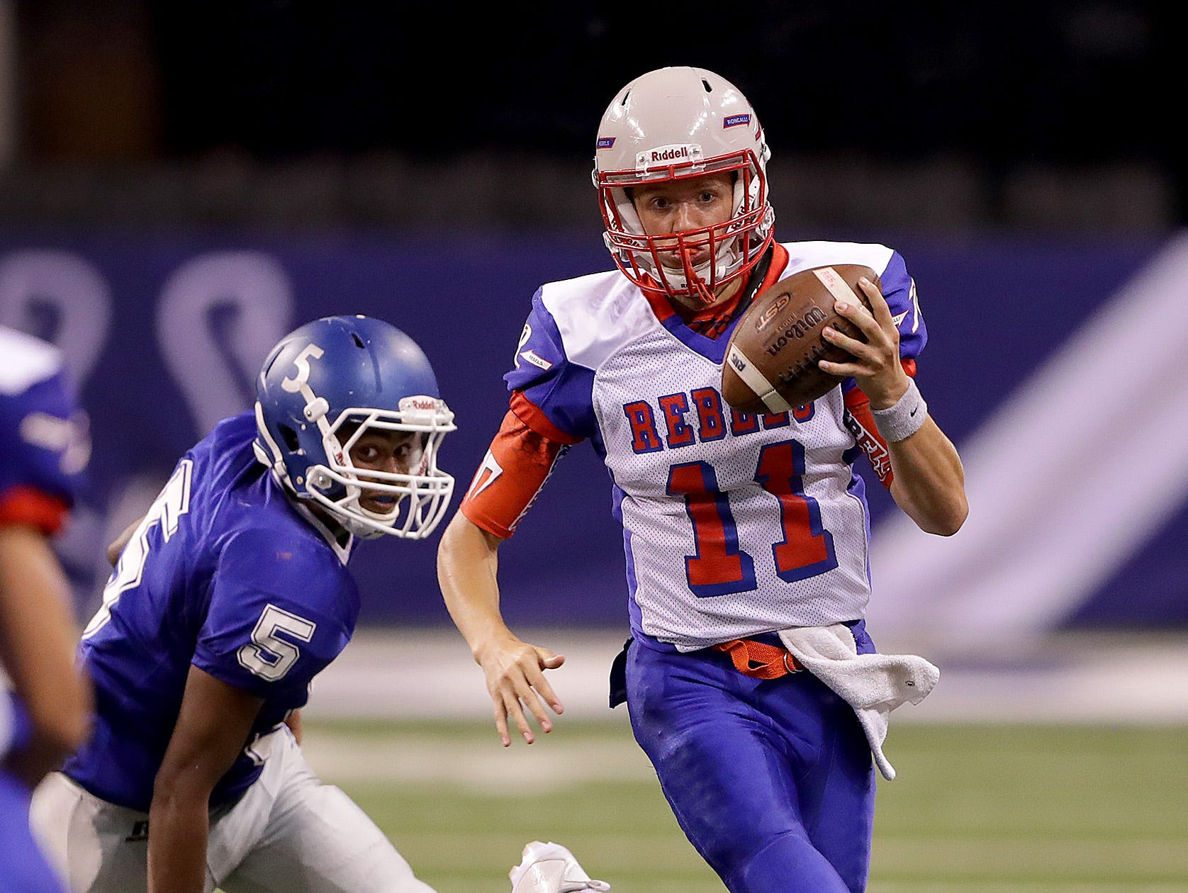 Roncallli's quarterback Derek O'Connor (11) runs by Franklin Central's Kajuan Coe (5) in the second half of their game. The Roncallli Rebels defeated the Franklin Central Flashes 22-14l Friday, August 26, 2015, evening at Lucas Oil Stadium.