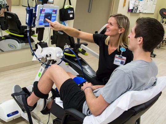 Brinley Johnson, Martin Health Physical Therapist, works with Chase Rushlow using the RT300 Cycle.