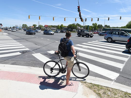 A bicyclist waits to cross at the newly renovated crosswalk as A ceremony was held on Monday June 13th at Coastal Highway & Lighthouse Plaza Drive north of Rehoboth Beach to mark the completion of the Coastal Highway (Del. Rt. 1) pedestrian safety project.  Delaware Governor Jack Markell and Secretary of Transportation Jen Cohan were on hand to cut a ribbon with several other local and state dignitaries.