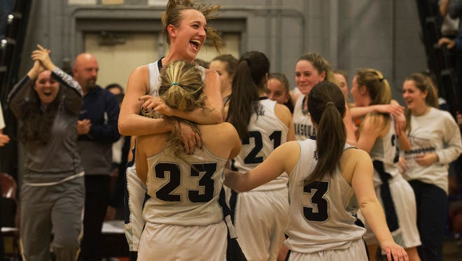 Manasquan's Dara Mabrey leaps into the arms of teammate Erin Howard as they celebrate their championship. Rumson-Fair Haven vs Manasquan Girls Basketball in the Central Group II championship game in Manasquan, NJ on March 8, 2016
