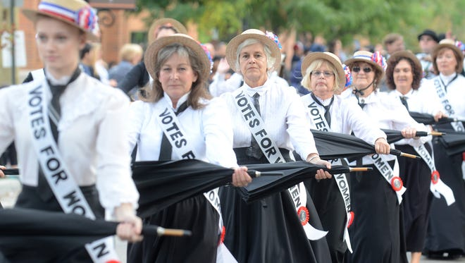 The Parasol Drill Team marches down Wing Street during the Northville Heritage Parade. The drill team urged for the vote of women with their signs.