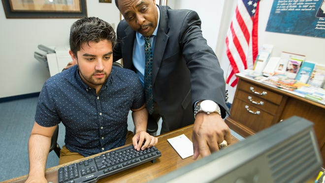 Las Cruces Hispanic Chamber of Commerce vice president Curtis Rosemond, right, works with Greg Delatorre, office assistant, on Wednesday, March 30, 2016.