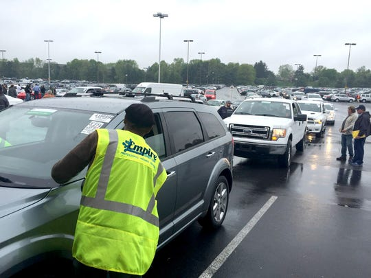 An employee of Manheim Auto Auction prepares one in a long line of vehicles that were sold during last week's auction.