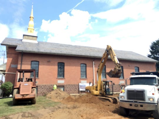 An excavator digs a hole at St. Benedict the Abbot Church in Lebanon, where an elevator is going to be installed to make the church accessible to the disabled.