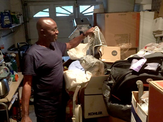 Charles Kyeremeh Sr. moves items stored in his North Cornwall Township home that were donated to a foundation his family created in memory of his son, Charles Jr., who died in a motorcycle crash five years ago. The items including clothing, shoes and books will be shipped to a village in Ghana, where Kyeremeh grew up.