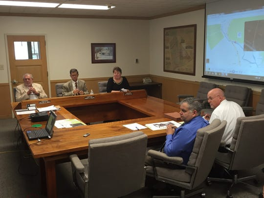 The Lebanon County commissioners (rear from left) Bill Ames, Bob Phillips and Jo Ellen Litz listen to PennDOT engineer John Kennedy (front from left) and project manager John Bachman discuss a plan to preserve and replace the Inwood Bridge near Lickdale.
