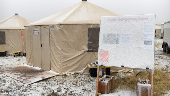 Snow covers up the fire information board at fire camp for the Alice Creek fire in Montana. Fire officials says the snow and rain is helping to contain fires that have raged across the state all summer.