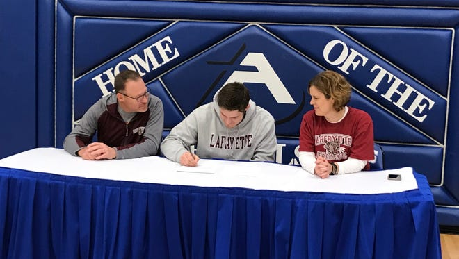 Assumption senior Joe Grundhoffer, flanked by his dad Greg and mom Kay, signed a letter of intent to play football at Lafayette University in a ceremony Wednesday at Assumption.
