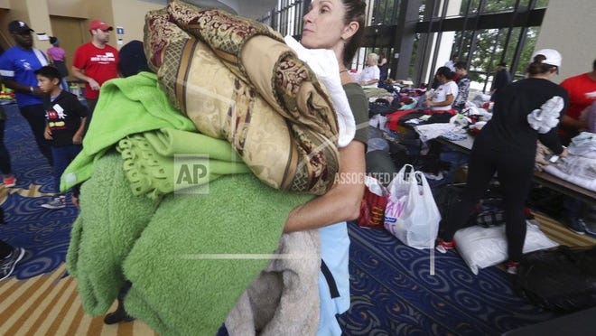 Volunteer Judy Segar carries donated blankets for victims of the flooding from Tropical Storm Harvey at a shelter opened at the Lakewood Church in Houston, Texas, Tuesday, Aug. 29, 2017.