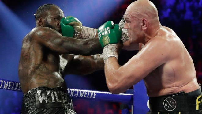 From Feb. 22, 2020, Tyson Fury, of England, lands a right to Deontay Wilder, left, during a WBC heavyweight championship boxing match in Las Vegas. Boxing promoter Bob Arum says he plans to stage a card of five fights on June 9 at the MGM Grand. It's the first of a series of fights over the next two months at the Las Vegas hotel. A second fight card will be held two nights later. ESPN will televise both cards to kick off twice weekly shows at the hotel in June and July. The fights are pending approval of the Nevada Athletic Commission.