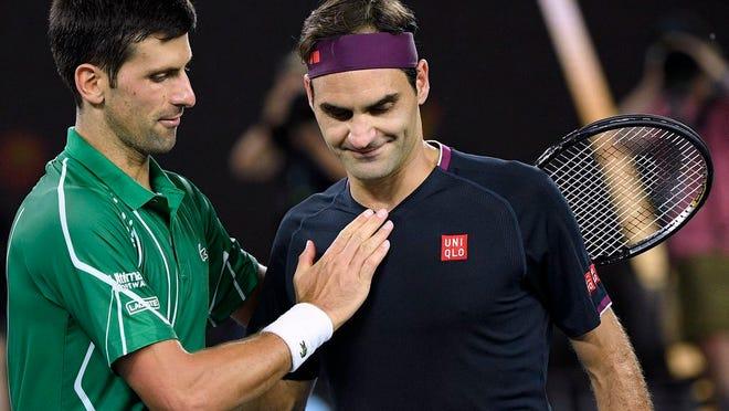 Switzerland's Roger Federer, right, congratulates Serbia's Novak Djokovic on winning their semifinal match at the Australian Open tennis championship in Melbourne, Australia, Thursday, Jan. 30, 2020.