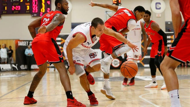 Former Ohio State guard Aaron Craft (4) of Scarlet & Gray dribbles between opponents during a The Basketball Tournament second-round game in 2018 at Capital University.