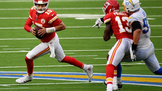 Quarterback Patrick Mahomes, left, of the Kansas City Chiefs scrambles against the Los Angeles Chargers in the second half of an NFL football game at SoFi Stadium in Inglewood, Calif., on Sunday, Sept. 20, 2020.