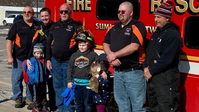 Austin Fisher, then 8, wears a firefighter helmet as he poses with members of the Summerfield Township Fire Department Feb. 14 at Summerfield Elementary School. The department honored Austin for heroic actions that may have saved his mother's life.