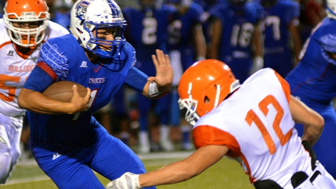 Las Cruces High quarterback Kameron Miller stiff arms an Artesia Bulldog defender on Friday night.