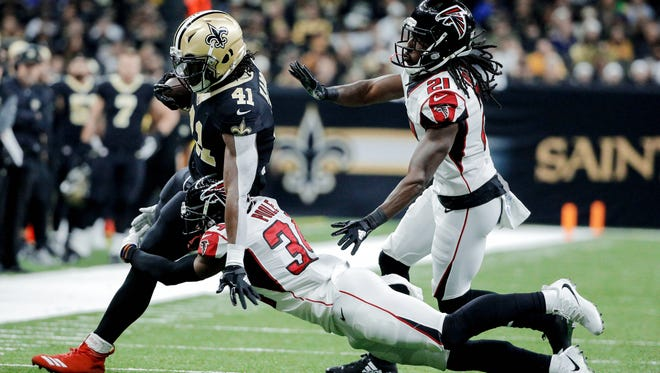 New Orleans Saints running back Alvin Kamara (41) is tackled by Atlanta Falcons cornerback Brian Poole (34) and cornerback Desmond Trufant (21) during the first quarter at the Mercedes-Benz Superdome.