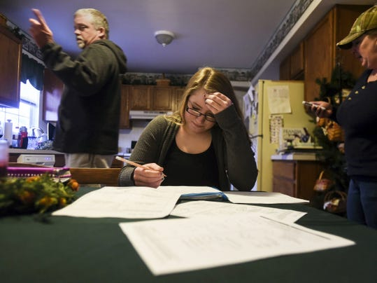 Kristin Reed, 15, works on her mathematics homework at the kitchen table March 24 at her home in Littlestown. Reed was once an honor roll student, now suffering from five concussions Reed struggles daily to maintain her grades in school. Her family, mother Stacy Reed, stepfather Kenneth Tull, and older brother Jeffrey Reed, frequently find time to help Kristin with her studies. (Shane Dunlap — The Evening Sun)