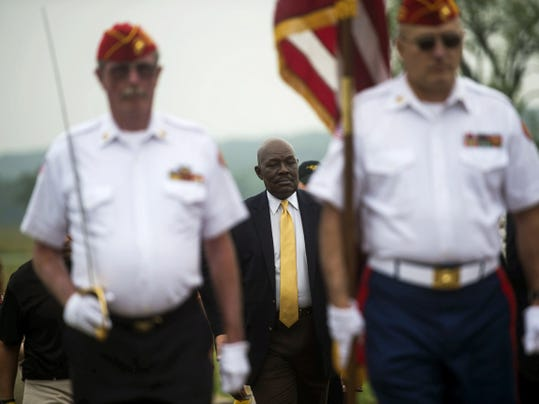 Rev. Mychal Massie of Orlando, Florida walks behind the Marine Corps League Honor Guard during the beginning of the Healing and Reconciliation of the Races event hosted by ATLAH World Missionary Church on Saturday in Gettysburg.