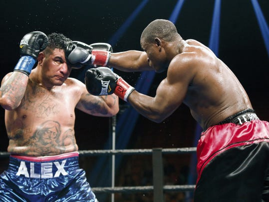 MARK LAMBIE—EL PASO TIMES  Fred Kassi connects to the forehead of Chris Arreola in their heavyweight bout Saturday at the Don Haskins Center. The fight ended in a draw.