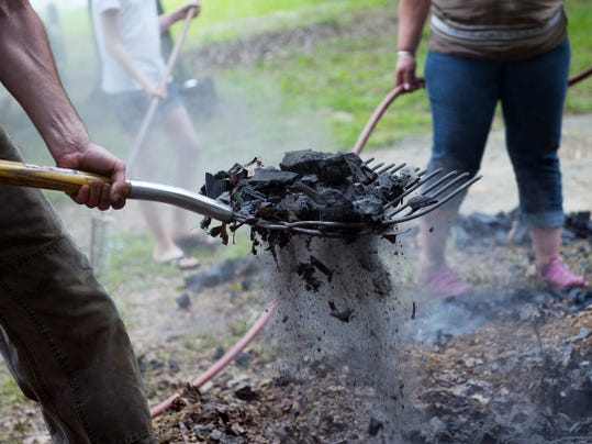 A volunteer shovels a forkful of ash and embers on June 7.