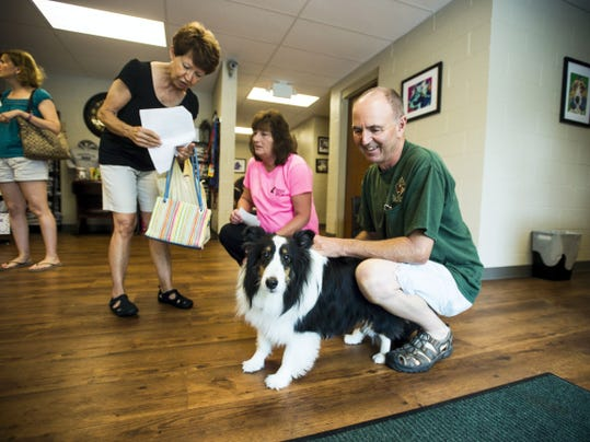 Gary Thomas, right, of Bendersville, holds his 9 year-old Sheltie, Chloee , while his wife, Karen Thomas, left, visits with staff at the newly renovated Adams County SPCA facility. Gary and Karen Thomas adopted Chloee from the Adams County SPCA five years ago.