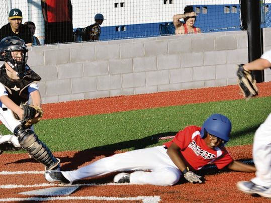 Matt Hollinshead — Current-Argus American Red right fielder RJ Amos beats the tag at home plate in the top of the second inning Sunday against National Blue. American Red will face Shorthorn Green at 6 p.m. Monday for the 10-year District All Star tournament championship.