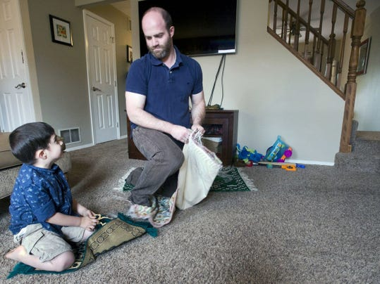 Zain Sharif, 3, looks up to his dad Aqil after prayer at their Newberry Township home. Muslim families are preparing to observe Ramadan, which begins Thursday.