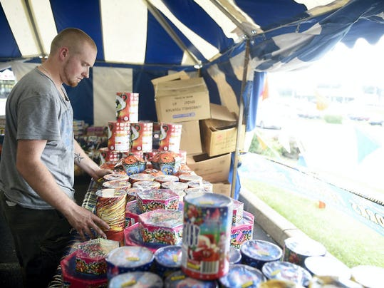Michael Fiske arranges merchandise at a temporary fireworks tent at Quentin Circle in North Cornwall Township. He and Joshua Gilbert are operating the short-term business, one of several such tents that have sprung up around the country as the Fourth of July grows closer.