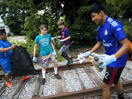 Hanover High School soccer team members from right, Diego Aguilar, Chris Kauffman and Izaiah Bosse, and parent Rafael Aguilar, left, collect litter around the rail tracks intersecting Broadway on June 6 in Hanover. Coach Soji Otuyelu says he intends to hold another day of volunteer work for the team in August before their regular seasons picks up.