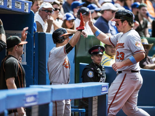 Baltimore's Travis Snider, right, celebrates with teammates after scoring on a single by J.J Hardy against Toronto during the seventh inning of Sunday's game in Toronto. The Orioles totaled 16 hits and won, 13-9.