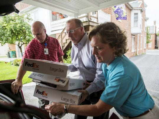Glenn Miller, middle, vice president of external relations for SpiriTrust Lutheran, helps Ginny Davis, right, and Dan Summers, left, both with the Adams County branch of SpiriTrust, take boxes of donations into Gettysburg Presbyterian Church on Tuesday morning in Gettysburg.