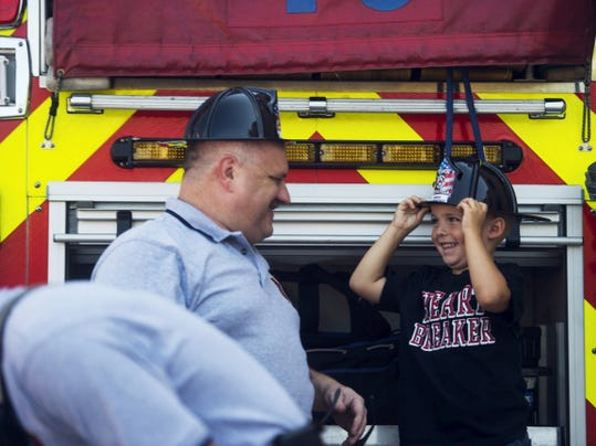 Brayden Bucher, 4, of Hanover, smiles up at Capt. Tony Clousher with Hanover Fire Department during a tour of a fire truck at the Guthrie Memorial Library parking lot Friday morning.