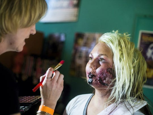 Corina Bange, of Littlestown, gets a zombie makeover by makeup artist MiChele Williams, with the special effects company Paramedic Zombies on Saturday for Timeline Arcade's first Arcade Horror Fest in Hanover.