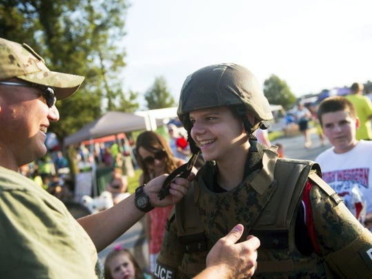 Brandon Augustine, 14, of Hanover, reacts as Penn Township Officer Rob Gaylord weighs him down with gear during Hanover's Night Out on Tuesday. Gaylord said the kids were trying on the heavy entry gear that members of the York County Quick Response Team use in barricade situations.