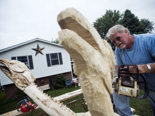 Jake Albright, of Penn Township, carves the head of a dragon sculpture with a chain saw Friday on Cardinal Drive in Hanover. The sculpture, a commissioned piece carved from a maple tree, is one of the largest the Hanover-area chain saw artist has undertaken so far.