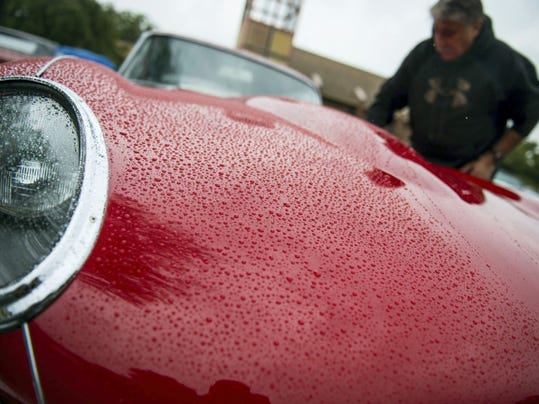 """Harold Zabady wipes off his 1964 Jaguar E Type. Despite the rain Saturday, The Knights of Columbus Council 9875 held its first """"Cruise for a Knight"""" car show at St. Paul the Apostle Church in Annville to benefit local charities."""