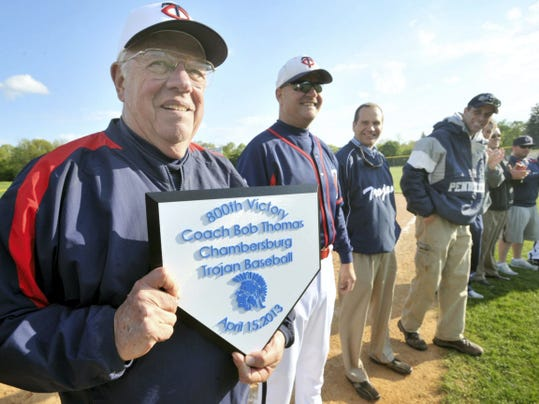 Chambersburg baseball coach Bob Thomas, left, holds a plague while joined by former players following a game on April 15, 2013 at Greene Township Park. The gathering was in recognition of Thomas' 800th career victory. Thomas resigned Tuesday after 51 years as the Trojans' head coach. He finished with 833 victories.