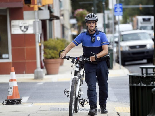 Officer Craig Leisher walks his bike Thursday in downtown Chambersburg. Officers will start enforcing of being off your bike on the sidewalks.