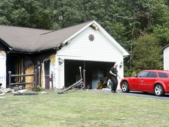 A fire investigator leaves the house at 6503 Mountain Drive in Fayetteville on Sunday afternoon after an alleged arson around 1:45 a.m. resulted in its destruction.