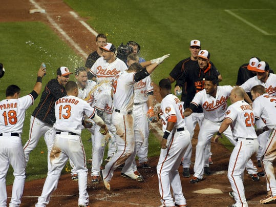 Baltimore Orioles teammates celebrate Wednesday as Chris Davis reaches home plate after his second home run of the evening, a solo shot against the Tampa Bay Rays in the 11th inning that gave the O's a 7-6 win at Oriole Park at Camden Yards in Baltimore.