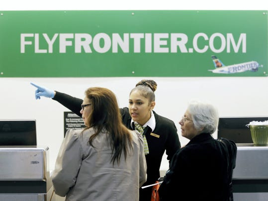 FILE - In this Oct. 15, 2014 file photo, a Frontier Airlines employee directs passengers at Cleveland Hopkins International Airport in Cleveland. There are few businesses that consumers love to hate more than airlines, but travelers seem to reserve a special level of vitriol for the no-frills, discount airlines. (AP Photo/Tony Dejak, File)
