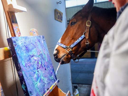 Metro Meteor works on an abstract painting in 2014 with owner, Ron Krajewski.