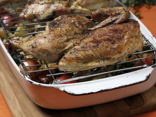 The chicken halves roast on a rack over the vegetables, ensuring crisp skin for the bird, and deeper flavor for the vegetables as the juices drip into them. (E. Jason Wambsgans/Chicago Tribune/TNS)