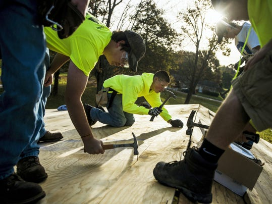 Gettysburg Area High School juniors and students with the Building Trades Program Derren Hunsicker and Aaron Van Houtte, background, hammer wood panels with fellow students for the new roof at the Gettysburg Lions Club pavilion at Gettysburg Area Recreation Authority park Wednesday morning in Gettysburg.