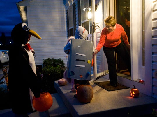 Denise Palmisano hands out candy to robot Joshua Schmitt and penguin Cassandra Weas during trick-or-treat night in West Manheim Township in 2012.
