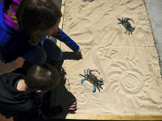 Anna Watson, 10, and her brother Noah, 5, draw in the sand at the mini-golf hole for Big Mike's Crab House, Schmuck Lumber Company and the Carriage House Market in downtown Saturday during the Main Street mini-golf tournament.