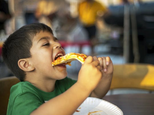 Dante Martinez, 5, of New Oxford, takes a bite of pizza at the Delone Carnival on June 10.