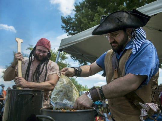 TJ Reese, left, and Jeff Trone add green chilis and onions to pots of chili at their booth, The Pirates of the Chilibbean, on Sunday during the annual Hanover Chili Cook Off on Sunday.